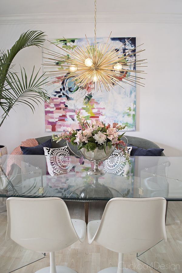 dining room with colorful art, velvet chaise, tulip chairs, glass table, urchin chandelier, palm tree and flower arrangement - Cuckoo4Design