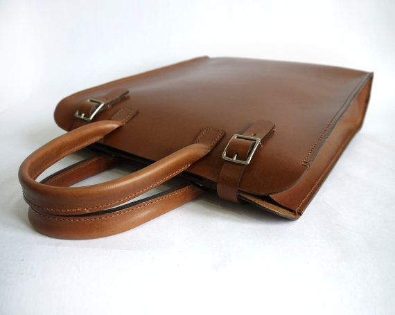"""This sleek leather tote couples a minimal aesthetic with a hint of vintage charm, the perfect accessory for a female or male wearer. Crafted from hand dyed vegetable tanned leather, the finish is supple yet durable, perfect for everyday wear. Featuring one main compartments, and a removable leather clutch, it's the perfect size for a 13"""" laptop, with more than enough room to spare. From professional to casual, it's a great bag for anyone who loves high quality materials and minimal styling…"""