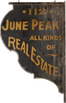 """Ornamental Sign for Texas Ranger June Peak's Dallas Real Estate Office. Measuring 25"""" x 37.75"""" x 1.25"""", this beautiful wooden sign sports scalloped edges enhanced by a silver border. The sign itself is painted black with gold lettering and reads """"112 / June Peak / All Kinds / Of / Real Estate."""""""