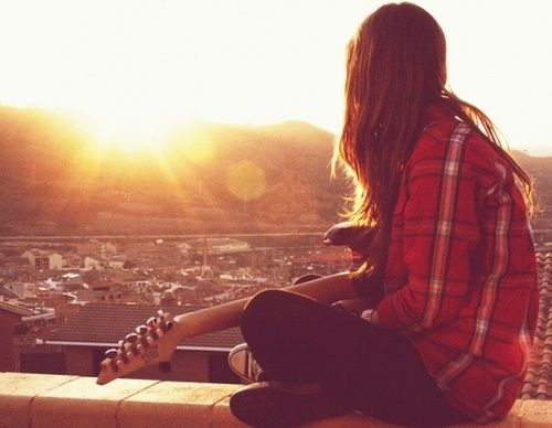 A girl holding a guitar peers out over a city skyline at sun set.