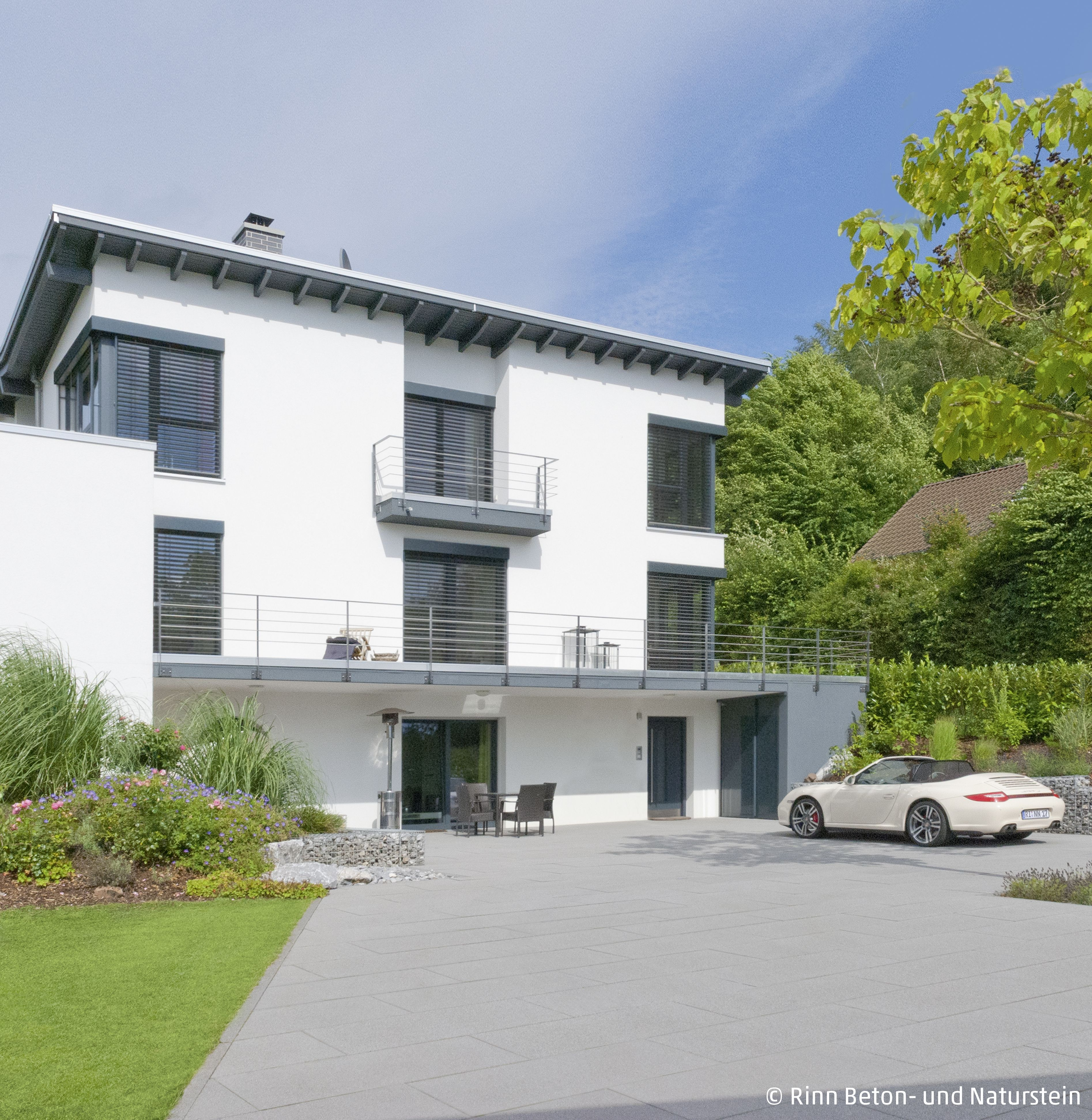 Moderner Zuruckgelegener Hofbereich Mit Autostellplatz Und PLatz Fur Baume Der Balkon Am Haus Bildet Ein