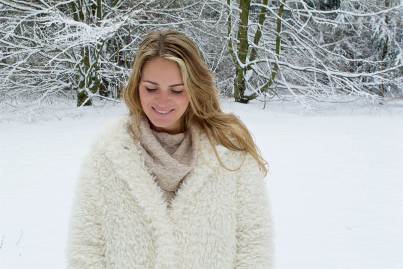 3d1e9d99ef2 Smiling blonde fashion and style blogger girl in closeup view wearing a  teddy bear coat with hood in a winter wonderland