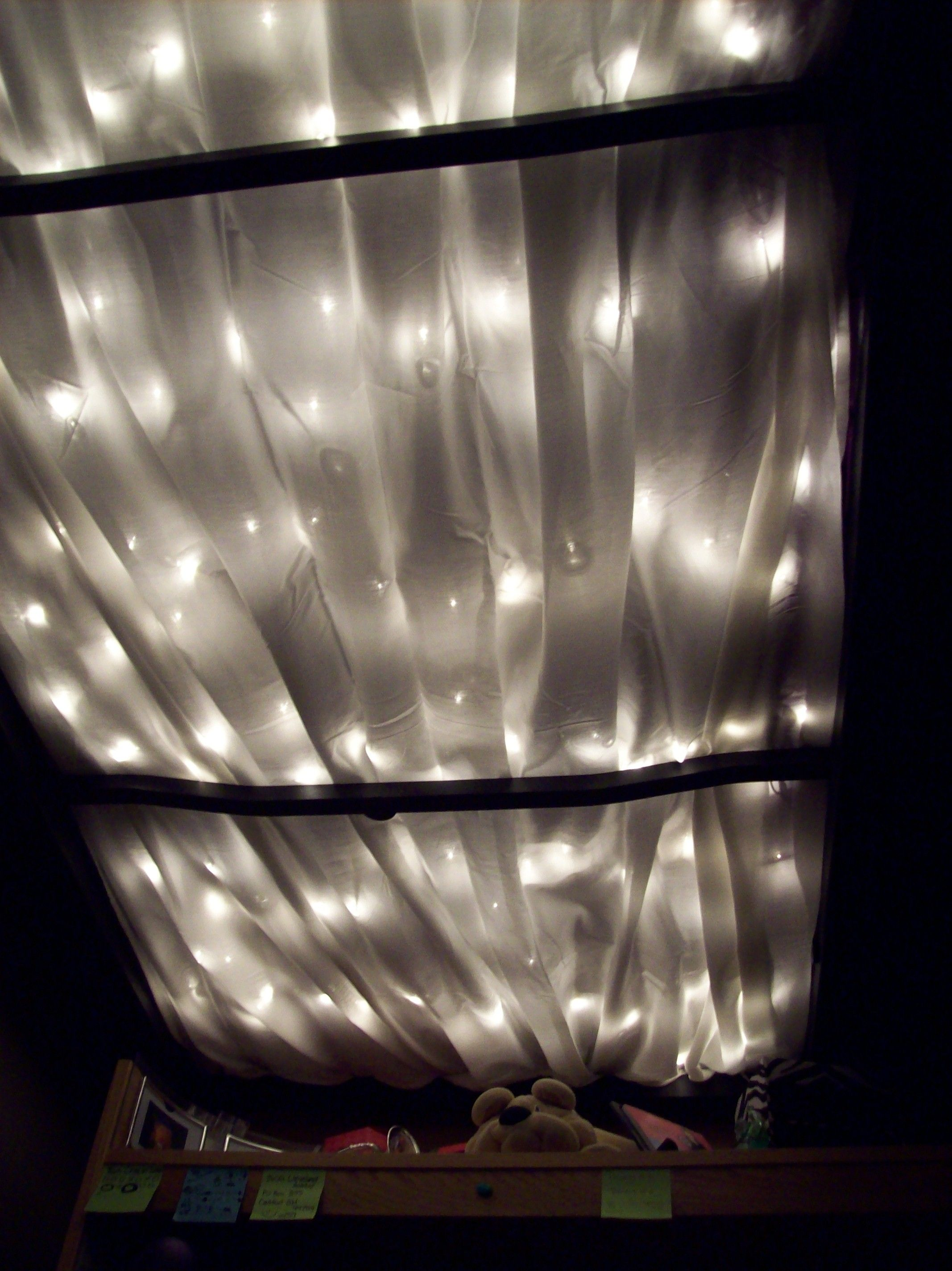Loft bed lighting ideas  white light strand and a white sheet draped under a college dorm bed