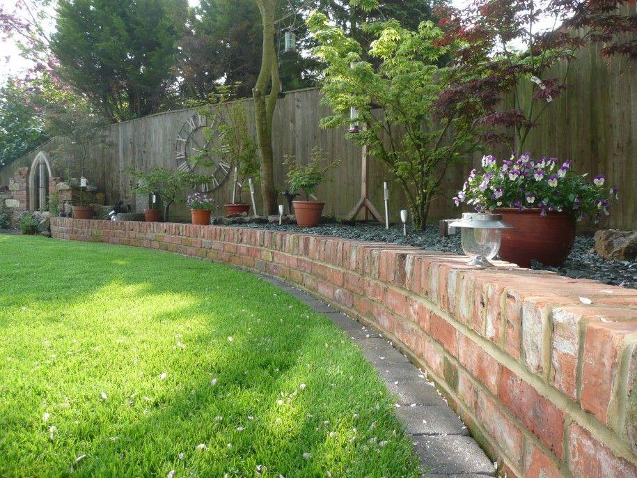 Brick green grass flowers pots wooden fence small garden for Red brick garden