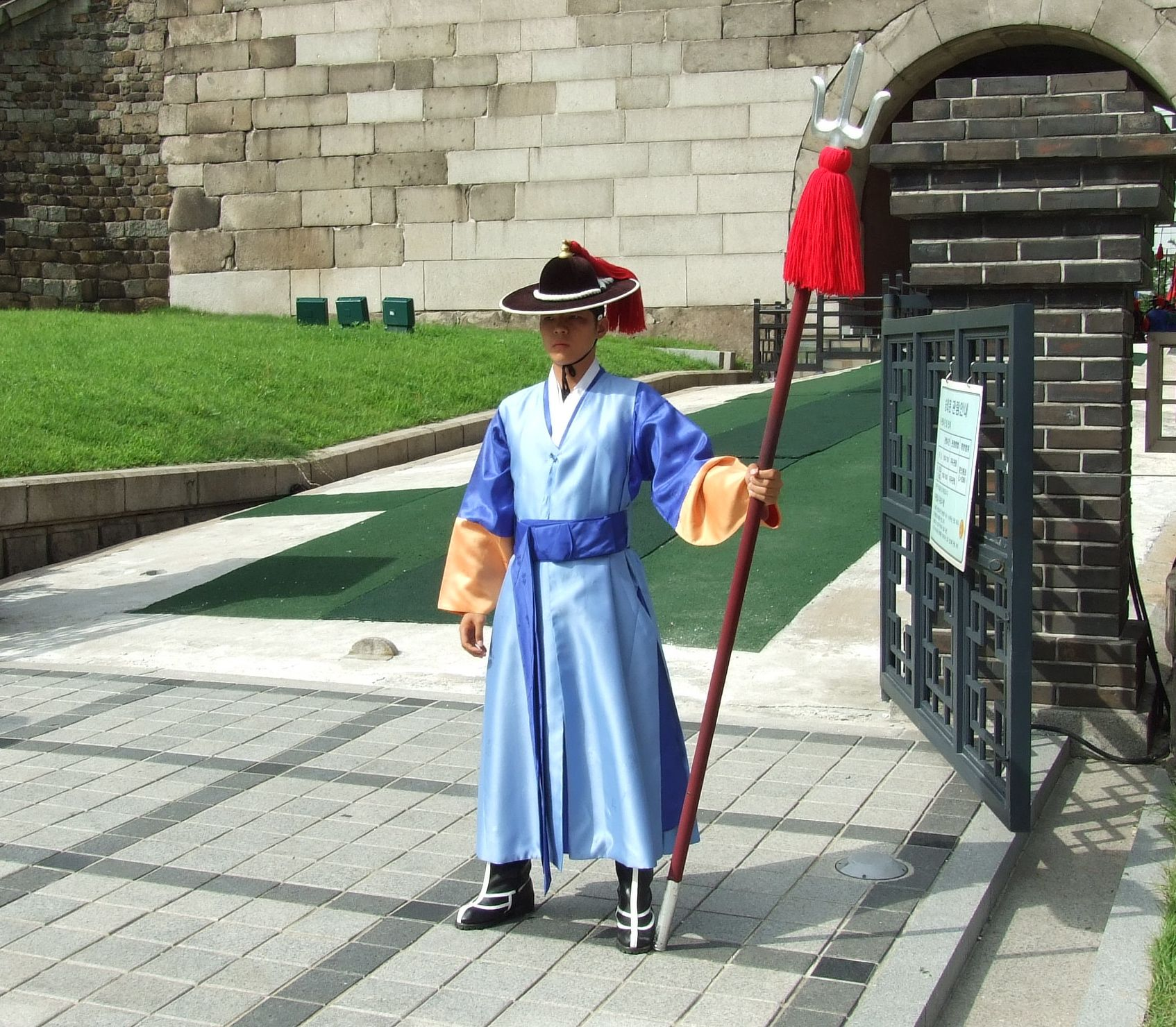 """The jeonbok is a type of sleeveless long vest in hanbok, traditional Korean clothing, which was worn by military personnel. It does not have overlapped column on the front side, and was worn over dongdari (동다리).[1] """"Korean guard with dangpa"""" by Kbarends - Own work. Licensed under CC BY-SA 3.0 via Wikimedia Commons - http://commons.wikimedia.org/wiki/File:Korean_guard_with_dangpa.JPG#/media/File:Korean_guard_with_dangpa.JPG"""