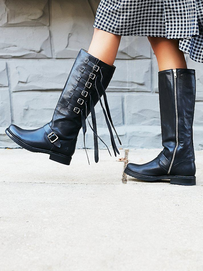 Veronica Tall Boot   Rugged and edgy moto style tall leather boots featuring statement buckle detailing on the side with fringe accents and silver hardware.  Rounded toe and stacked heel.