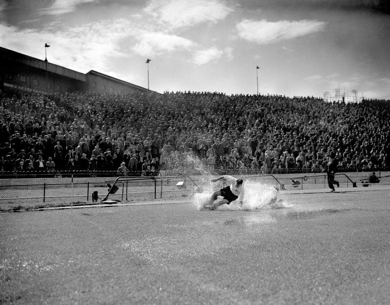 Tom Finney stumbles through a huge puddle after a downpour at Stamford Bridge, 1956. Believe it or not, Chelsea left-back Wally Bellet is also in there somewhere! The image won the 1956 Sports Photograph of the Year Award and went on to inspire 'The Splash' fountain/sculpture outside the National Football Museum.