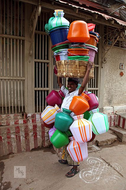 INDIA-  Vendor selling plastic  pots for water. Look at all the colors!  The orange and white stripes are common in the temples of South India. Also the steel  door stops unwanted people, but brings fresh breeze into the home.