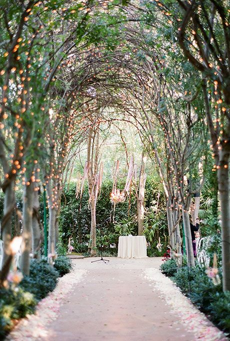 A Tree Lined Aisle Gets An Ethereal Upgrade With The Help Of Hundreds Ling Lights And Pastel Colored Flower Petals Brides