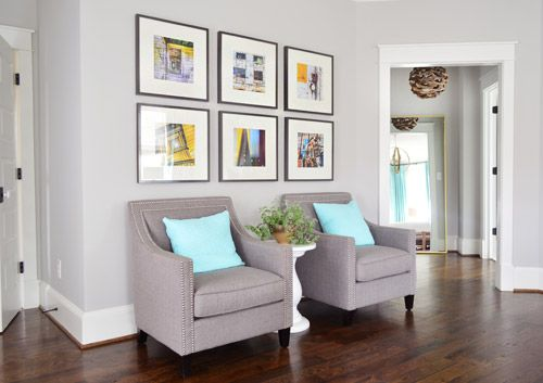 Master bedroom seating with pops of yellow in art aboe chairs. Business, Bedding, & Butlering | Young House Love