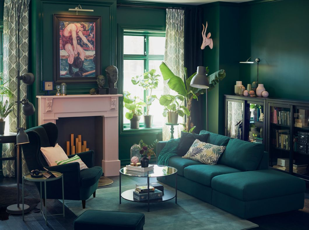 An Open Ended Dark Green Sofa Opposite An Armchair In A Green Living Room  With Pink Fireplace.