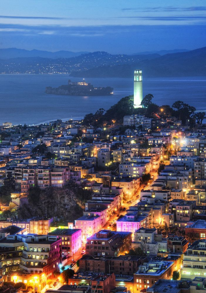 Alcatraz in the dusk...upstaged by the austere Coit Tower. San Francisco, California. Photo by Trey Ratcliff