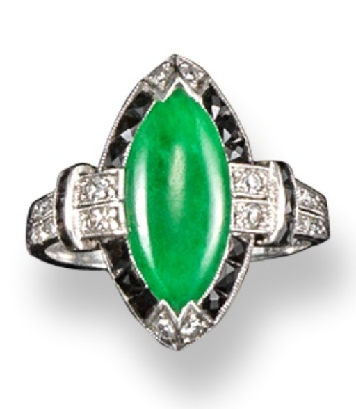An Art Deco jade and diamond ring, the marquise-shaped jade is set within a surround of square sections of black onyx and diamonds in platinum. With small diamonds set to the foliate engraved shoulders.