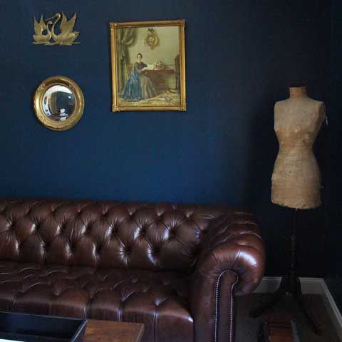 Navy Wall Decor brown leather chesterfield, antique mannequin and gold wall decor