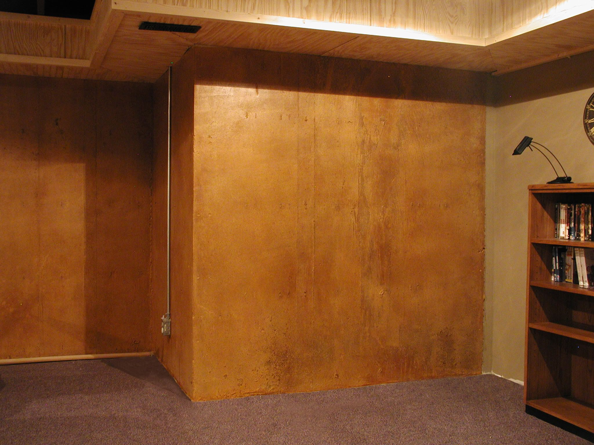 exposed concrete wall is acid stained in lieu of stone due to cost