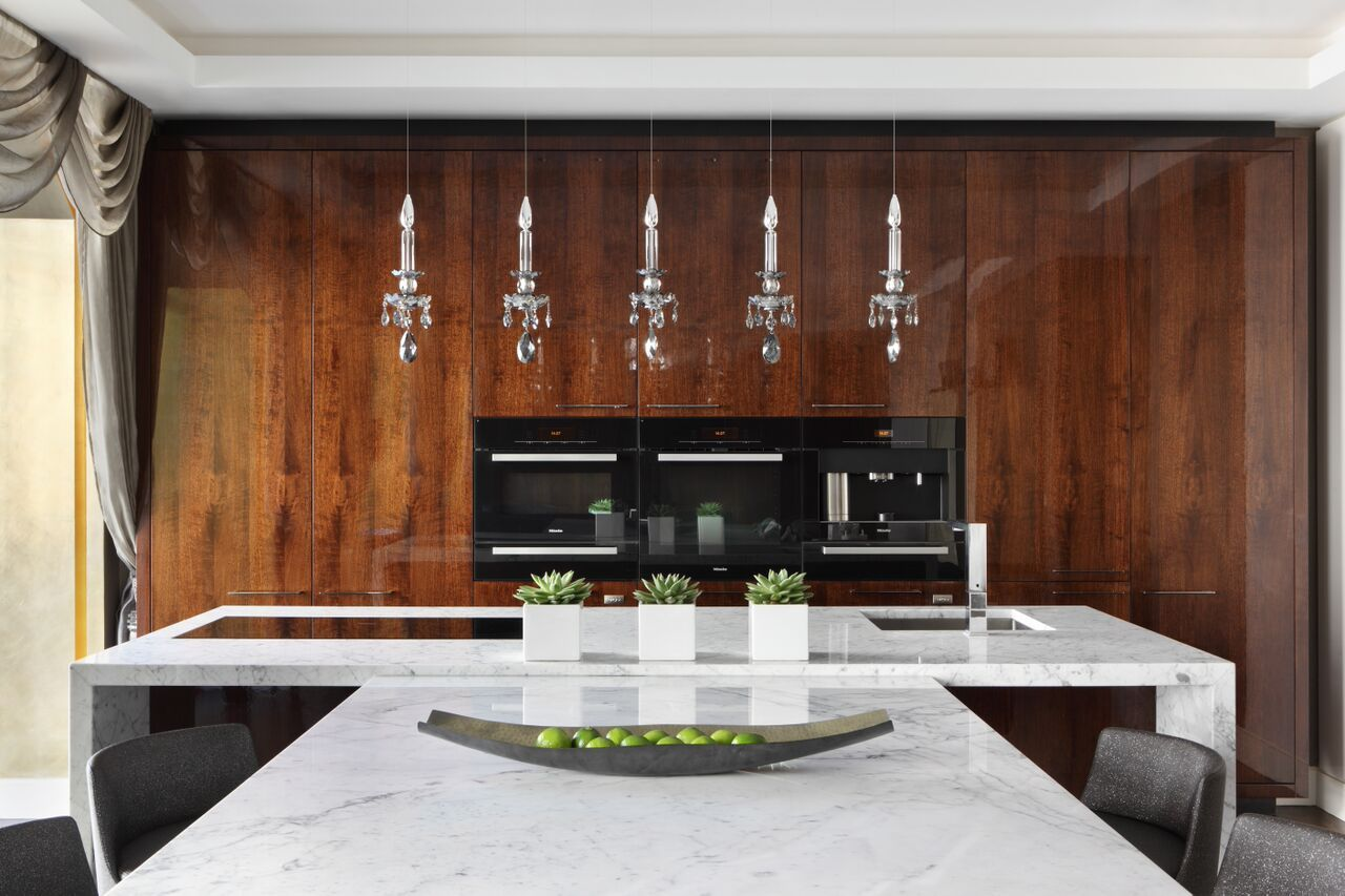 A kitchen featuring a glossy stained wood panel wall, contrasted by a white granite countertop, spanning out to form a dining table as well. Do you like the crystal pendant lamps? Designed by http://www.oliverburns.com/
