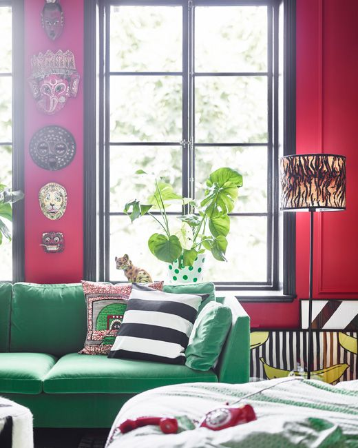 A green sofa and masks on the wall help give this dream bedroom it's own distinctive look