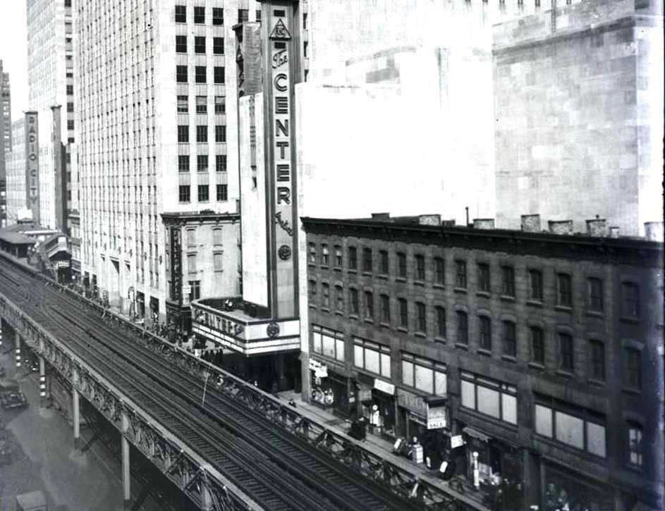 The Center was the little sister theater to Radio City Music Hall when they both were opened in 1932, it was demolished in 1954, the elevated tracks stood until 1939. The photo is at 6th avenue and 9th street. Radio City Music Hall in the background. 1934 photo.     New York Historical Society Museum and Library