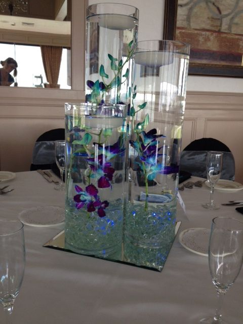 Cylinder Vases With Floating Candles And Submerged Blue Dendrobium Orchids Anchored With Clear