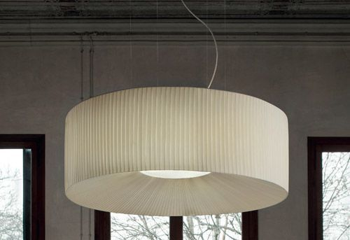 Round light with pleated cream fabric over a metallic frame. Conical internal position of fabric meeting inset diffuser.