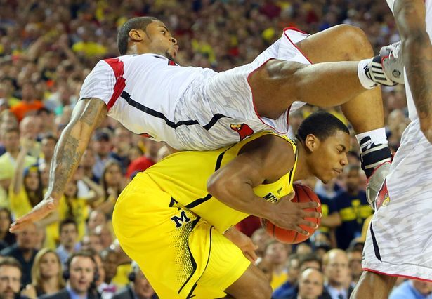 040813 ATLANTA: Louisville forward Chane Behanan comes down on top of Michigan forward Glenn Robinson III for a foul in the final minutes of the game. Louisvilled defeated Michigan to win the NCAA Division I National Championship on Monday, April 8, 2013, in Atlanta. CURTIS COMPTON/ CCOMPTON@AJC.COM