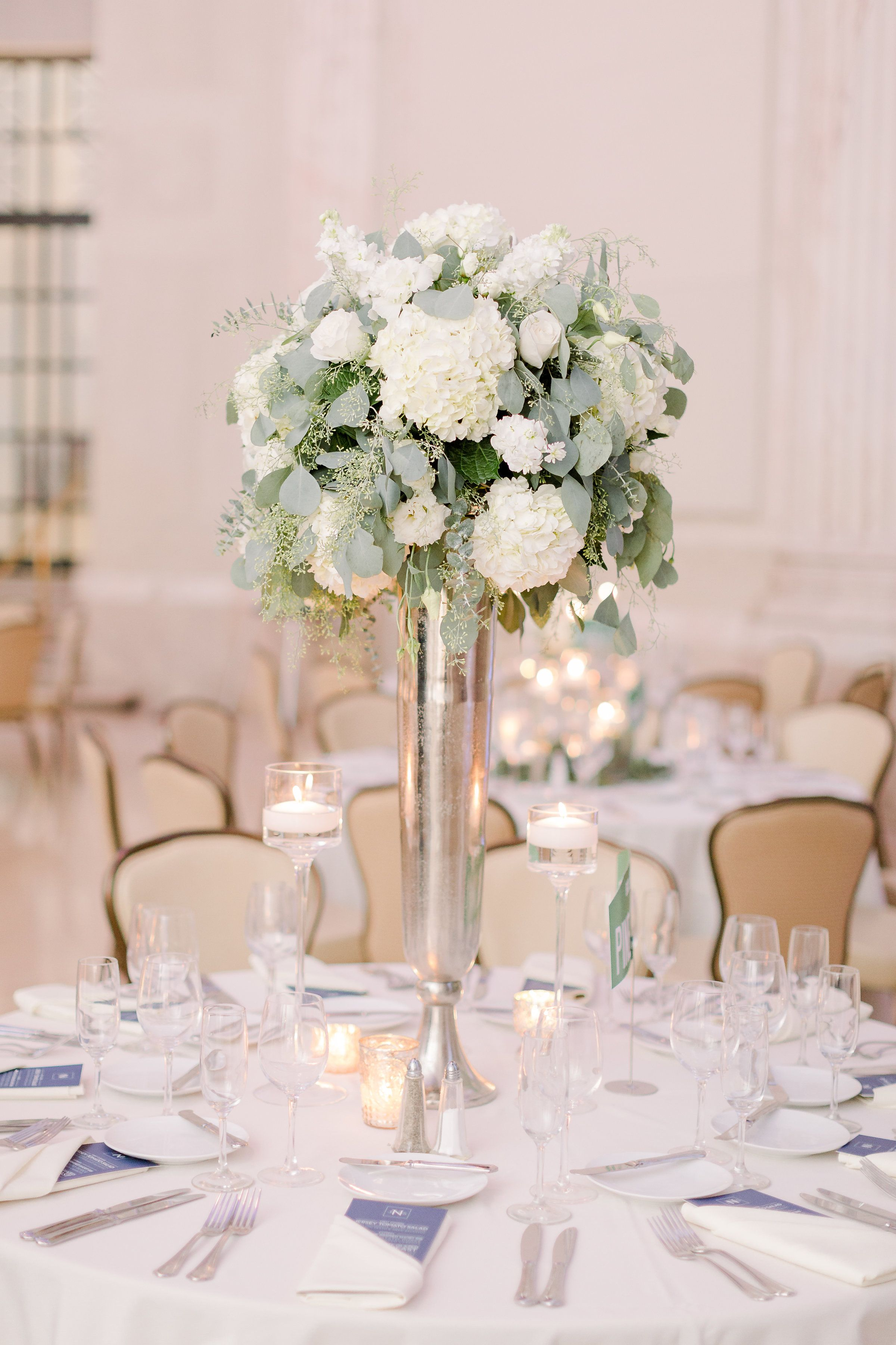 Tall White And Green Arrangement Nestled On Top Of A Silver Trumpet Vase Centerpiece Acce Floating Candles Wedding Tall Vase Centerpieces Wedding Centerpieces