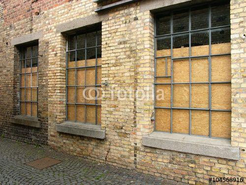 Spanplatten hinter alten Fabrikfenstern eines