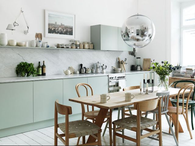 Dining room in eat in kitchen.  Thonet bent wood chairs. Trestle table.  Mirror ball pendant light.  Small kitchen with modern mint green cabinet doors, marble slab backsplash and floating shelves. http://cococozy.com