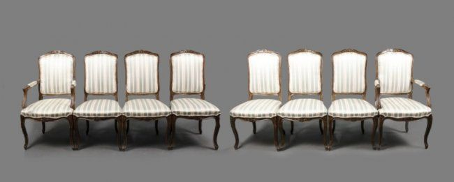 20th century. Set of eight matching Louis XV style walnut wood framed dining chairs (two armchairs and six side chairs). Each with floral decoration on shaped top , scrolled arms and similar floral motif on apron flanked by cabriole legs with leaf tip accented feet.