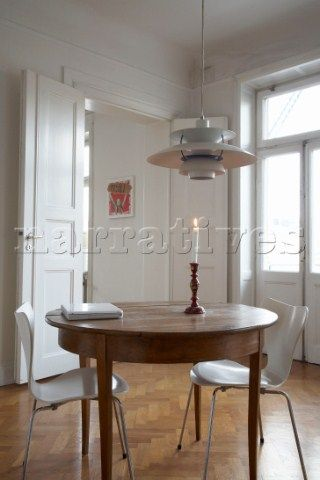 Wooden table with Arne Jacobsen chairs under pendant light by Poul