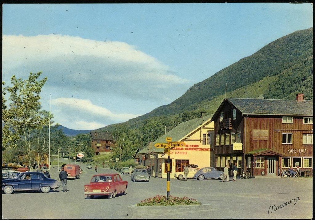 LOM sentrum i Oppland fylke, fargekort 1960-tallet med biler, skilt og handelsvirksomhet Utg Normann. Stpl. 1967
