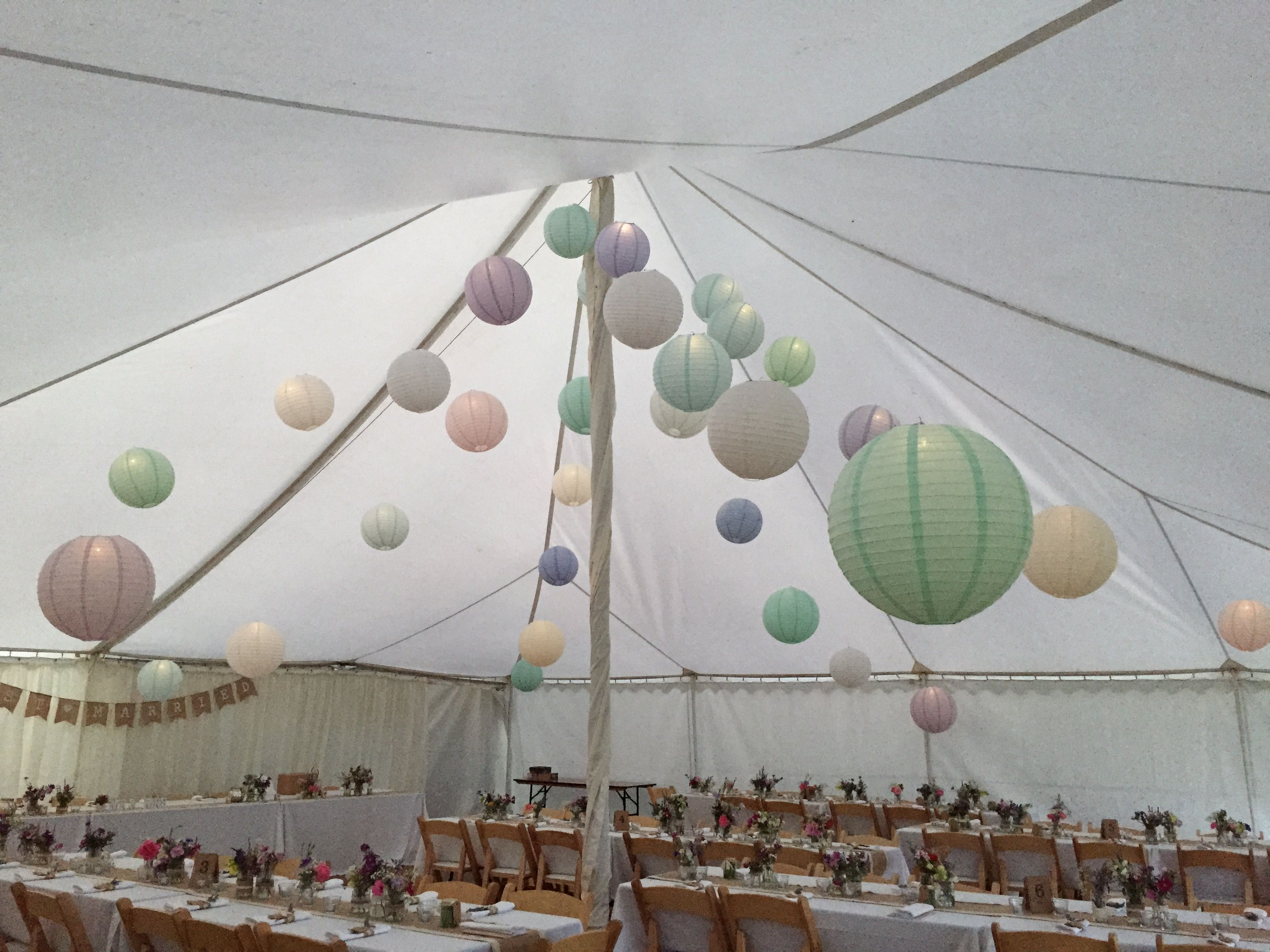 Choose pastels for a lighting extravaganza; paper lanterns with small bulbs, creating a look rather than a functional lighting use. Use uplights in the corners to create an evening 'glow' and fairy lights wrapped in organza to hide the unsightly pole and add more, delicate light. www.effervescenceevents.com