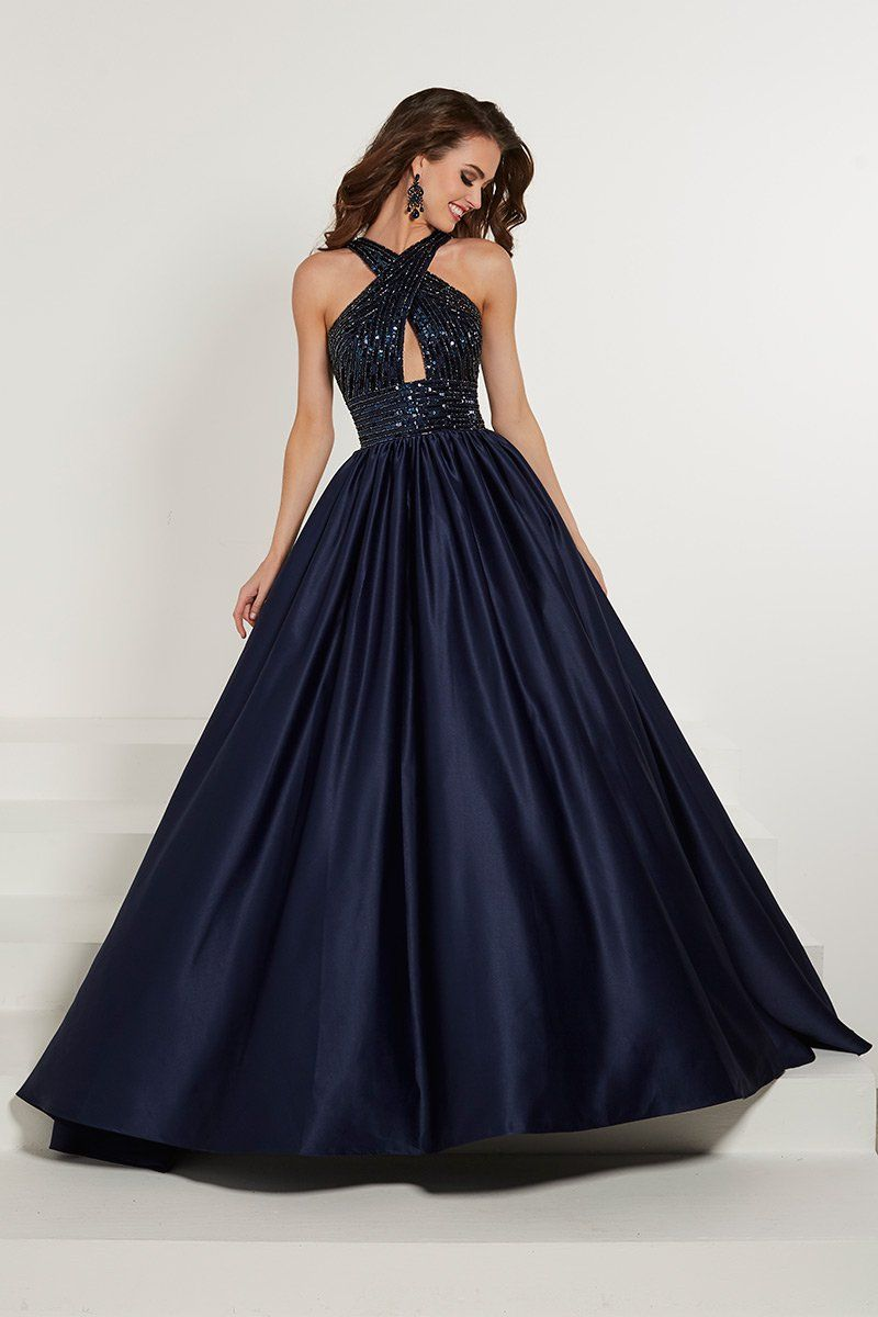 3219c110a42 Style 16327 from Tiffany Designs is a crossover halter neck prom gown that  has an asymmetric beaded bodice and waist line