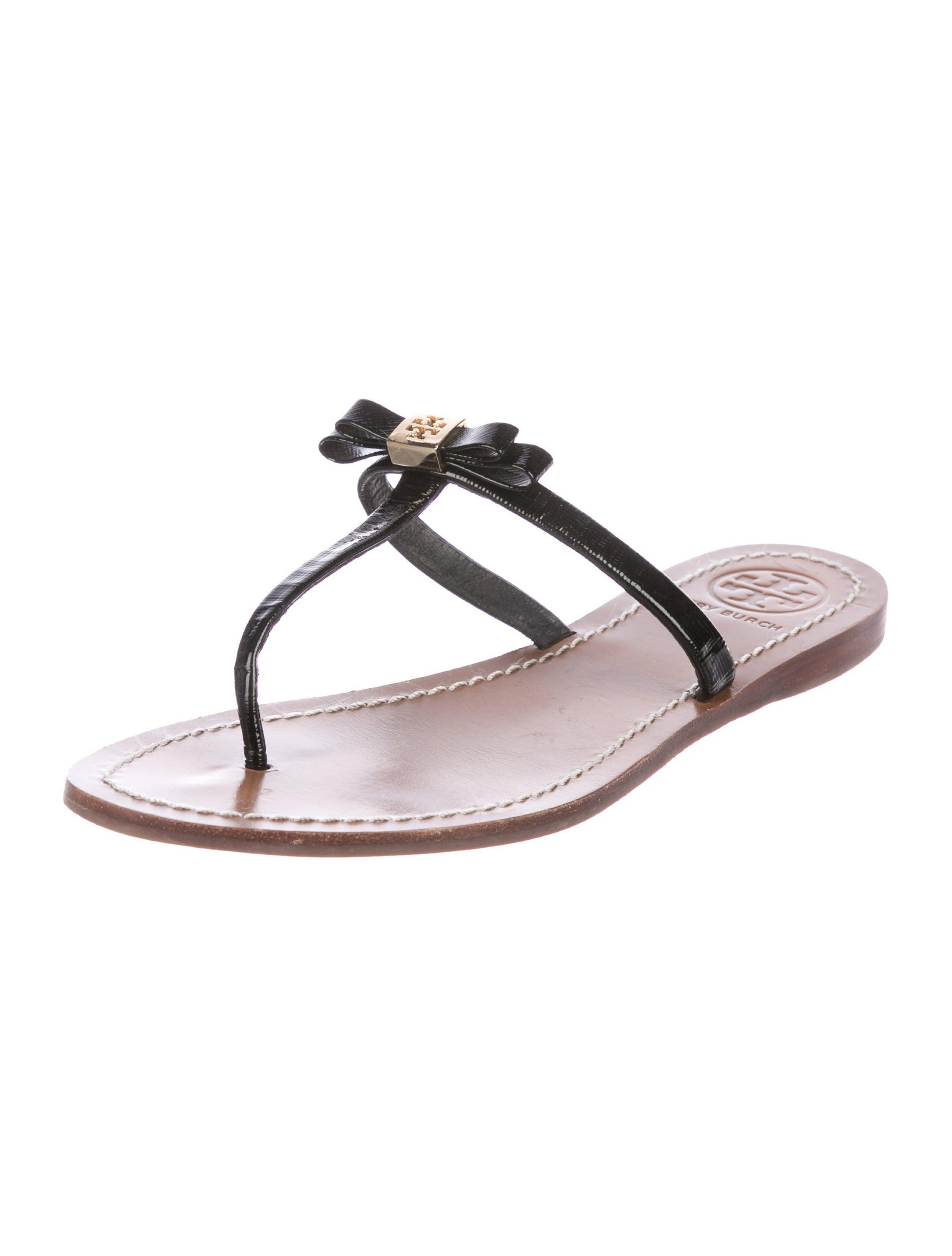 c2de267fa Black patent leather Tory Burch thong sandals with bow accents featuring  gold-tone logo embellishments at uppers and stacked heels. Size not listed