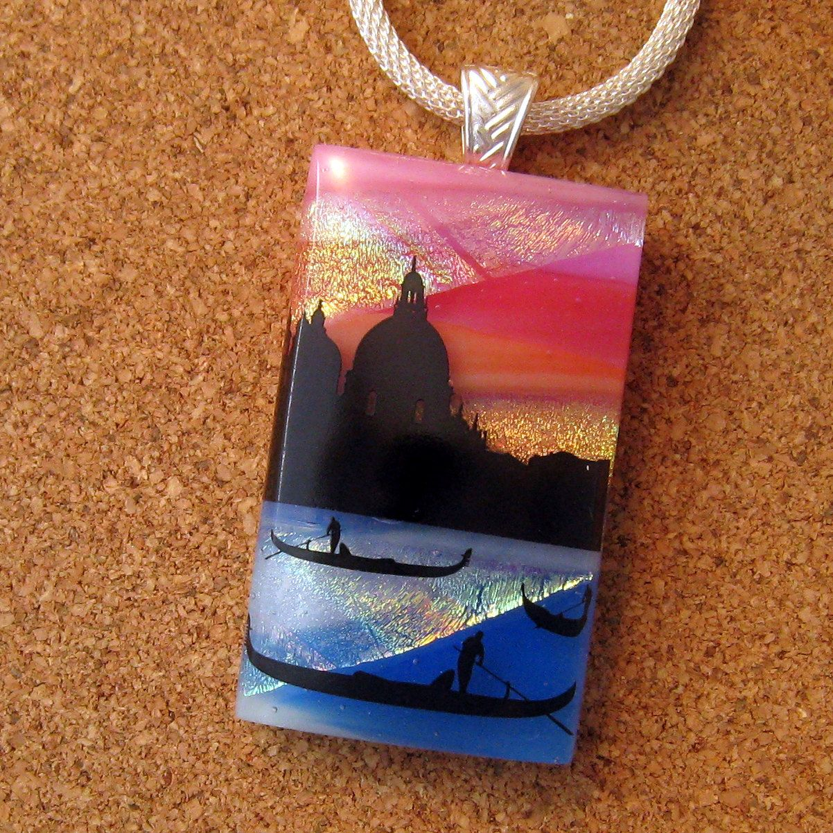 Glass fused pendant that has a landscape lake setting image.