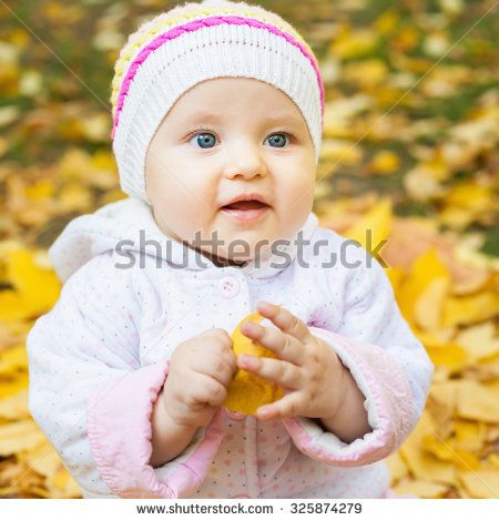 Happy baby or child outdoor at autumn park playing with yellow leaves - stock photo
