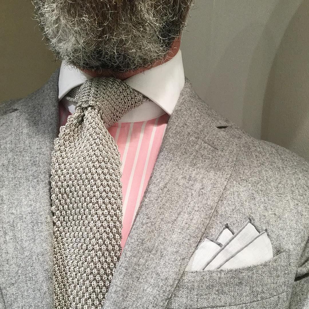Gray knit tie, pink shirt, gray bordered pocket square