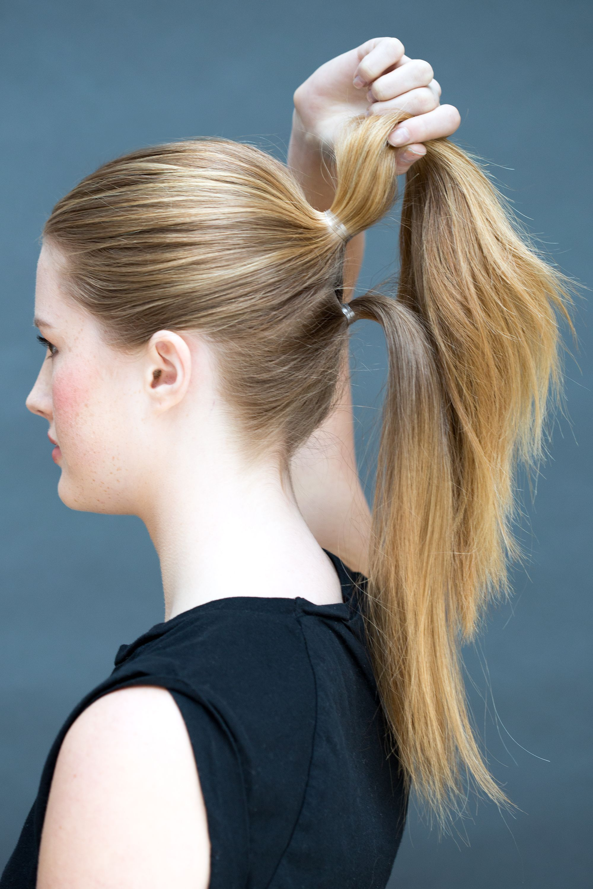 Pull the remaining hair into a pony right beneath the first one.   - MarieClaire.com