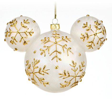 Mickey Mouse Ornament - Magic in the details... Winter wonder. Add a little fun to your elegance with this Mickey icon shaped ornament. Gold snowflakes on satiny white make a charming holiday statement, and this piece is sure to enhance the magic on any tree.   Created especially for Walt Disney World Resort and Disneyland Resort.   Bas relief snowflakes,  Gold thread for hanging.  The bare necessities:  Glass 4 1/2'' H x 6'' W.