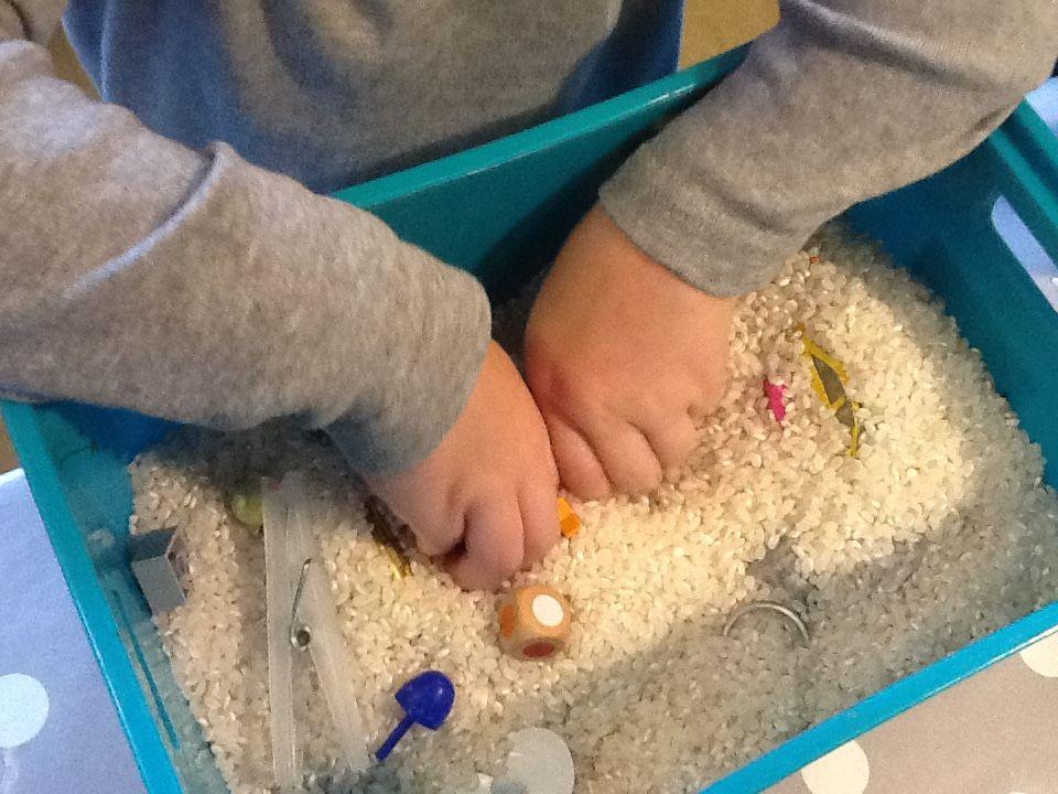 """Kasse med grødis, i kassen er der forskellige ting såsom.  En legoklods, sten, perler i forskellige former, nøglering, batteri, og andre små ting man bruger  i hverdagen.  Da der er lidt """"farlige ting """"som feks. batterier i , SKAL der sidde en voksen ved siden af."""