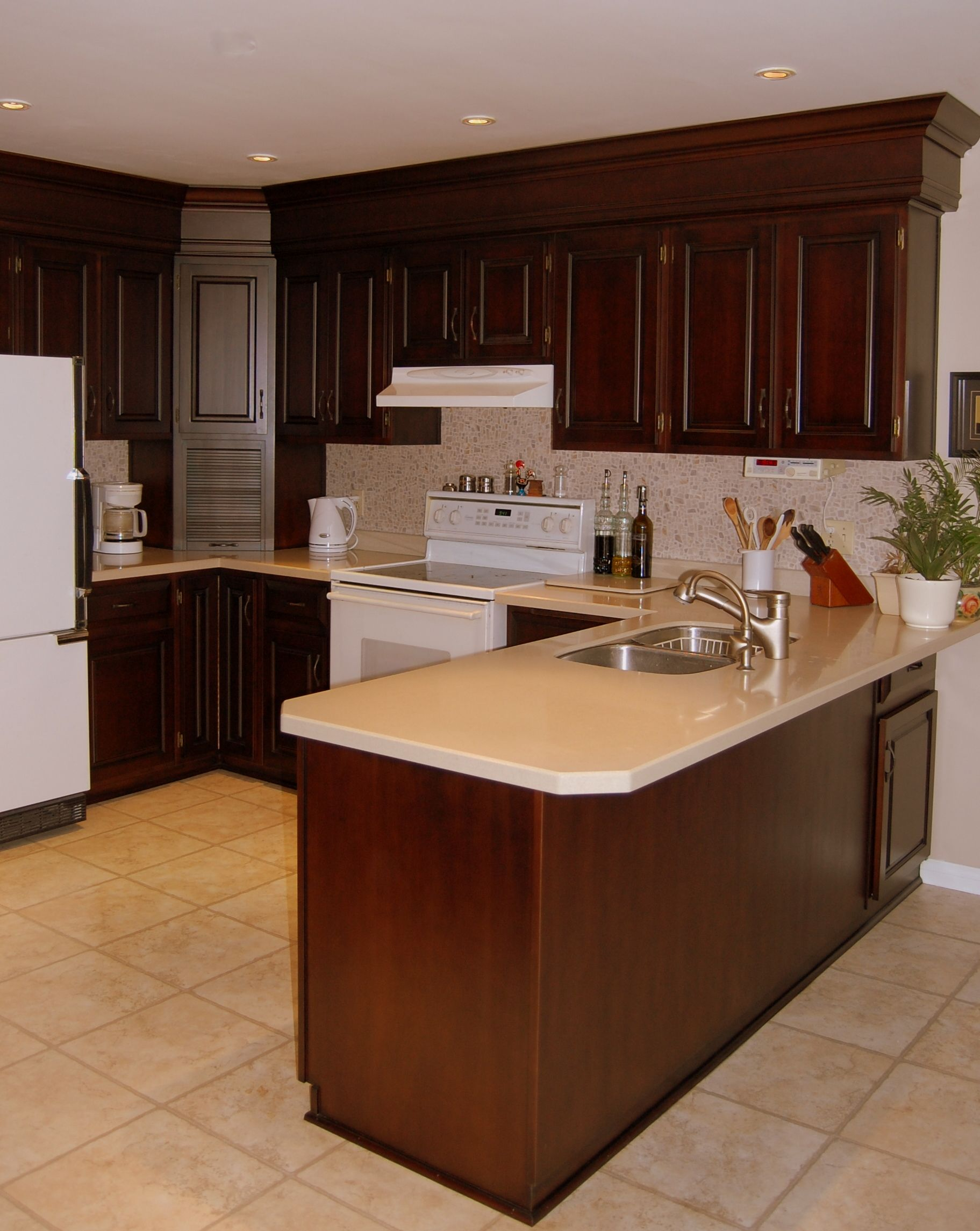 Cherry kitchen with two piece crown molding and paneling to cover