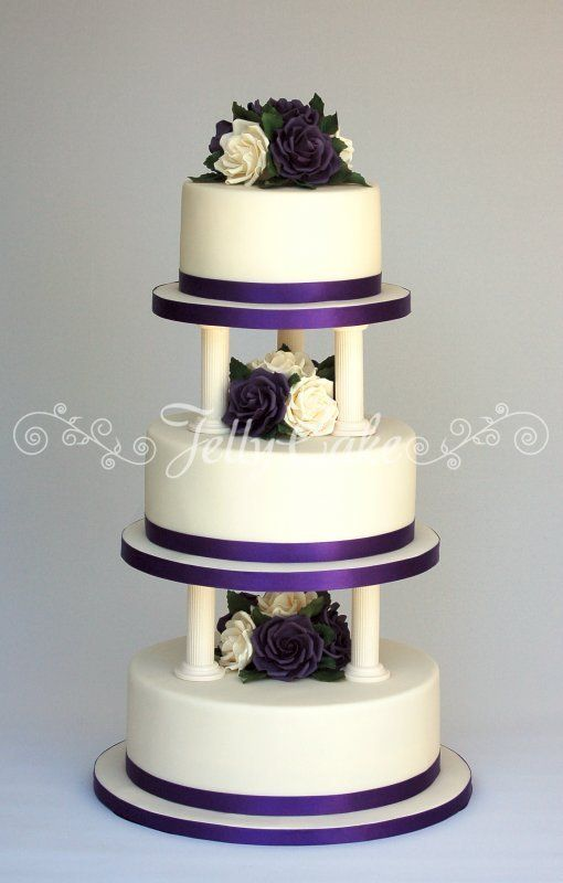 A 3 Tier Cadbury Purple And Ivory Wedding Cake With Sugar Roses Leaves Stacked On Pillars