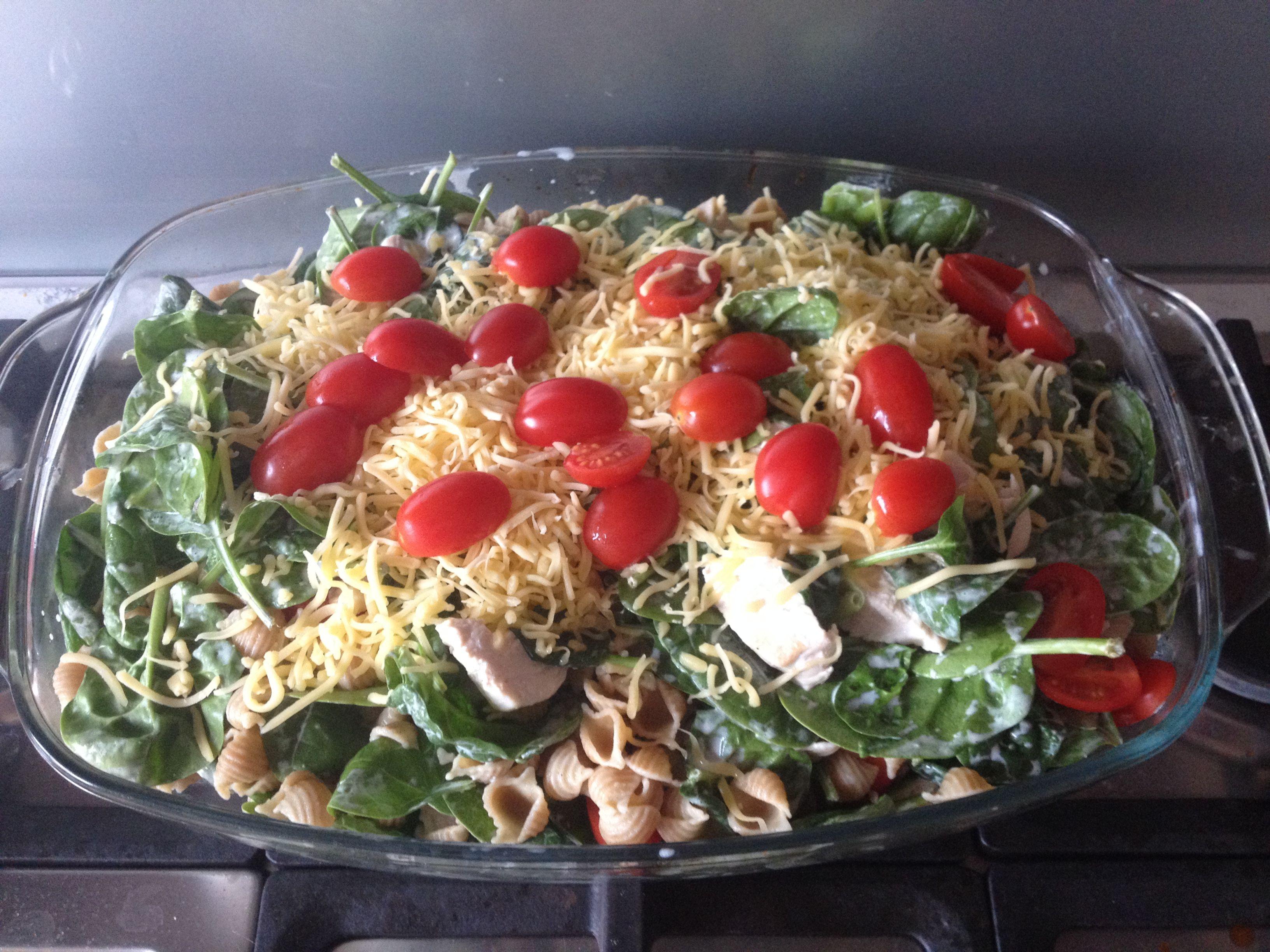 Spinazie pasta schotel: Volkoren pasta, cherrytomaten, kipfilet, lente ui, spinazie, kookroom, strooikaas.