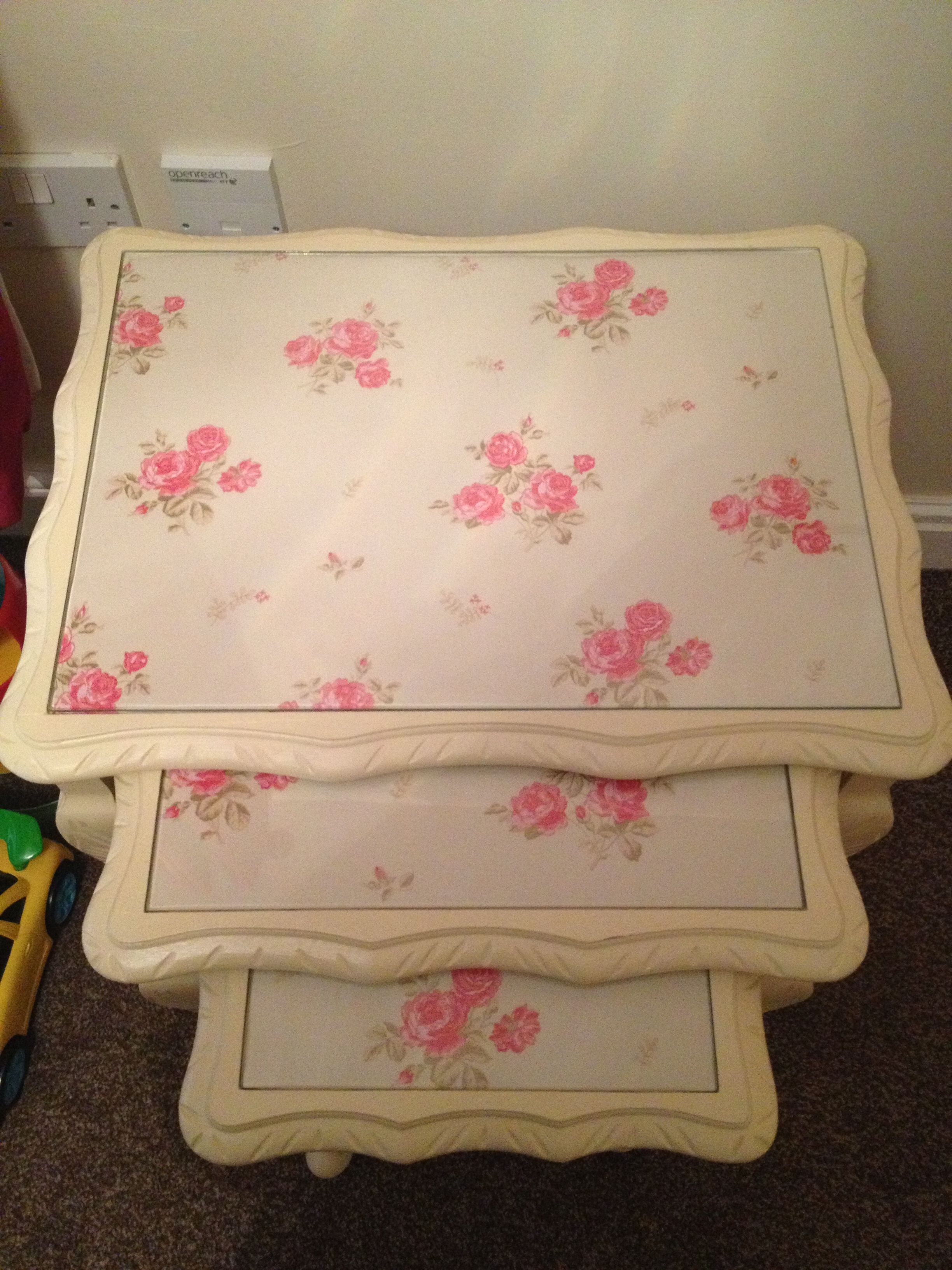 Shabby chic nest of tables painted in Annie Sloan cream with floral wallpaper under glass ...