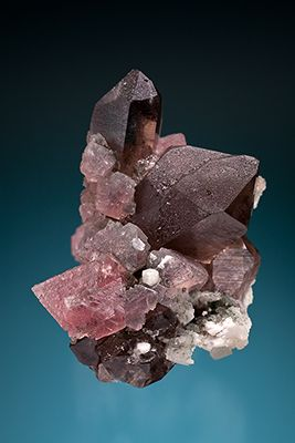 Pink octahedral fluorite crystals up to 1.5 x 1.3 cm perched on a cluster of smoky quartz and feldspar, associated with translucent white ad...