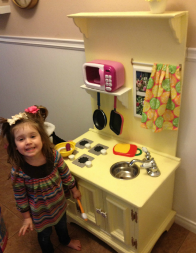 Just look how happy Ollie is to show off her little kitchen!