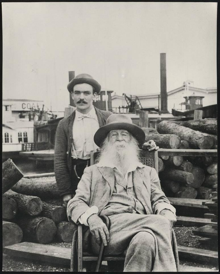 Walt Whitman, three-quarter length portrait, seated, facing front, with his nurse Warren Fritzenger, standing, and a pile of logs behind him, on the wharf, probably near his Mickle Street house in Camden 1890