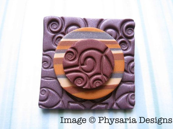 Polymer clay brooch in purple and orange.