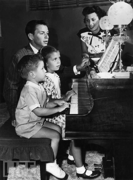 Frank Sinatre  overseeing a piano lesson with daughter Nancy and son Frank Jr.  while first wife Nancy Barbato looks  on...