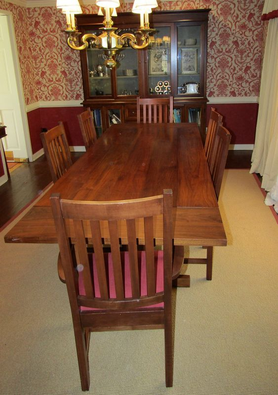 Modern dining room furniture including a mission style trestle table with 6 chairs, 4 side and 2 arm, and 2 leaves. With it is a contemporary hutch.